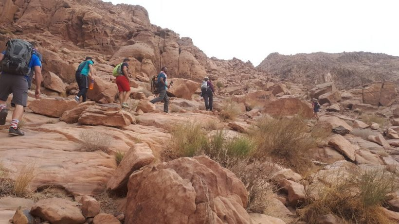 hikers making their way up a rocky slope on the silk road