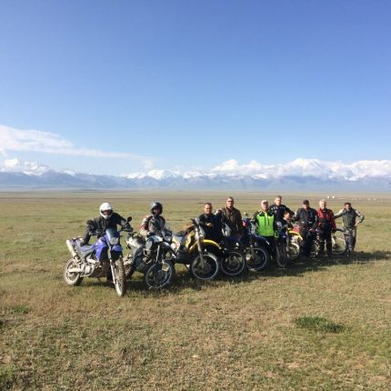 group photo of pamir motorcyclists in an open field