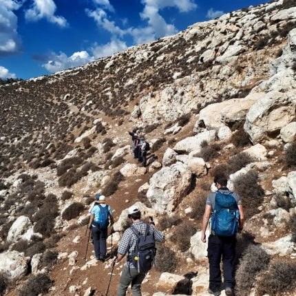people hiking up a hill near the Masar Ibrahim al Khalil